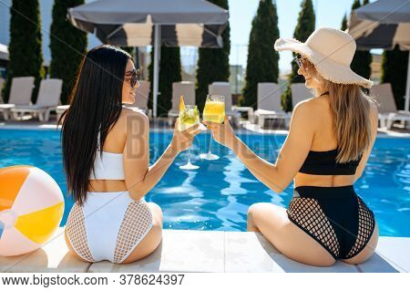 Sexy women with coctail at the poolside, back view