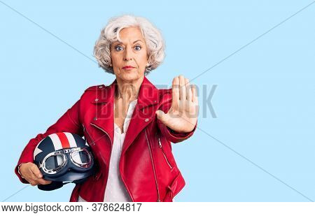 Senior grey-haired woman holding motorcycle helmet with open hand doing stop sign with serious and confident expression, defense gesture