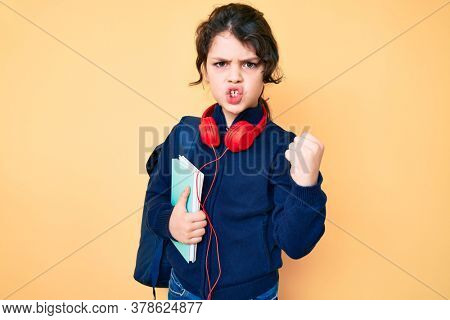 Cute hispanic child holding student backpack and books annoyed and frustrated shouting with anger, yelling crazy with anger and hand raised