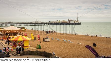Brighton, United Kingdom - june 26, 2018: Brighton Beach, Fair Ground And Pier On A Cloudy Day In