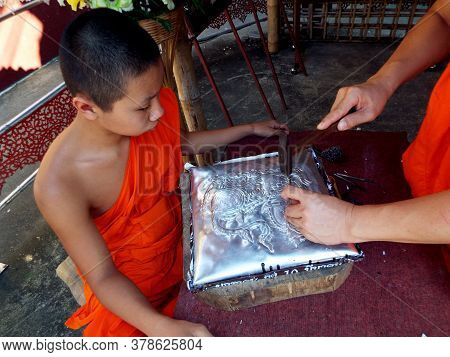 Chiang Mai, Thailand, December 6, 2018: Buddhist Monk Teaches His Student The Art Of Goldsmithing At