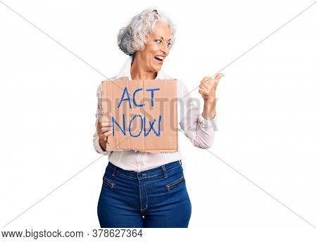 Senior grey-haired woman holding act now banner pointing thumb up to the side smiling happy with open mouth