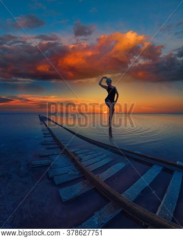 Woman at beauty sunset on salty lake with railway, concept of vacation at home, local tourism or domestic tourism