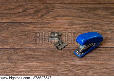 Blue Stapler And Staples On A Brown Wooden Background. For Business And Office.