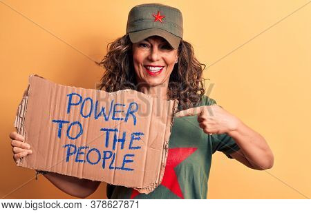 Middle age brunette communist woman holding banner with power to the people message smiling happy pointing with hand and finger