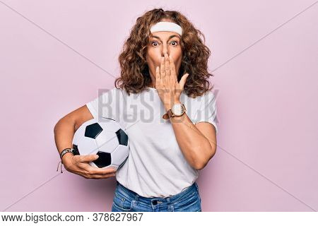 Middle age beautiful sporty woman playing soccer holding football bal over pink background covering mouth with hand, shocked and afraid for mistake. Surprised expression