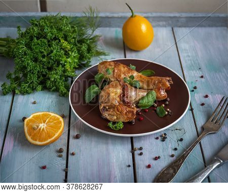 Baked Chicken Drumsticks With Fresh Parsley Sprigs On A Brown Plate On A Plain Wooden Tray