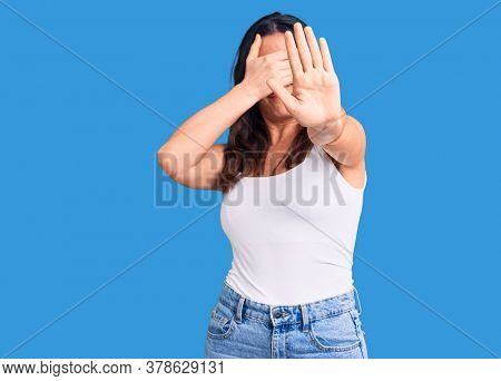 Young beautiful brunette woman wearing casual sleeveless t-shirt covering eyes with hands and doing stop gesture with sad and fear expression. embarrassed and negative concept.