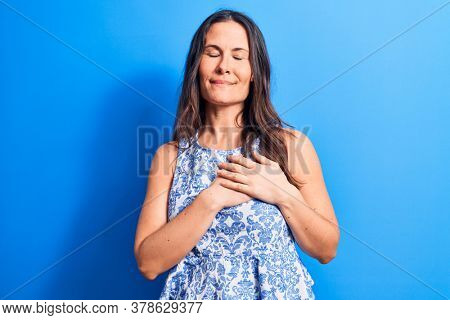 Young beautiful brunette woman wearing casual sleeveless t-shirt over blue background smiling with hands on chest, eyes closed with grateful gesture on face. Health concept.