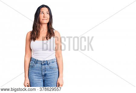 Young beautiful brunette woman wearing casual sleeveless t-shirt smiling looking to the side and staring away thinking.