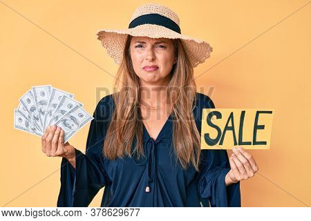 Middle age hispanic woman wearing summer hat holding sale banner and dollars clueless and confused expression. doubt concept.