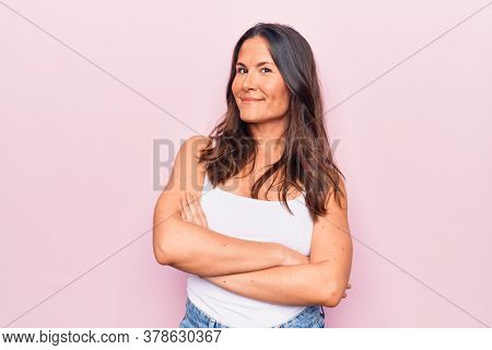 Young beautiful brunette woman wearing casual sleeveless t-shirt over white background happy face smiling with crossed arms looking at the camera. Positive person.