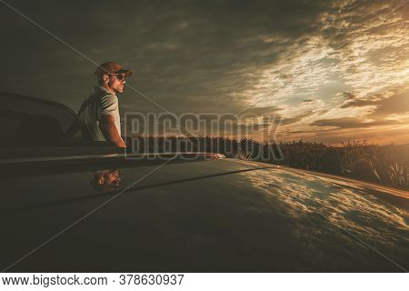 Travel And Lifestyle Theme. Golden Hour Scenic Drive Stop In Convertible Vehicle. Caucasian Men In H