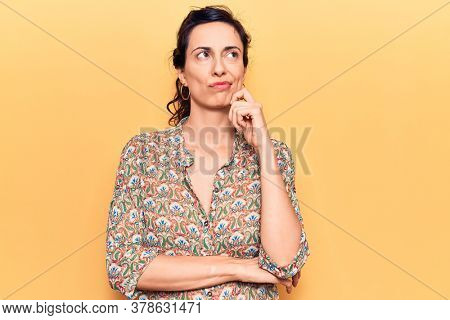Young beautiful hispanic woman wearing casual clothes thinking concentrated about doubt with finger on chin and looking up wondering