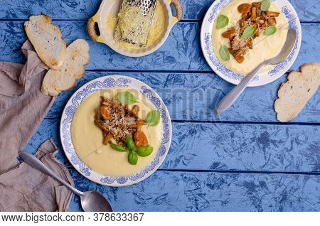 Traditional Polenta With Mushrooms And Cheese In A Dish On A Blue Wooden Background. Selective Focus