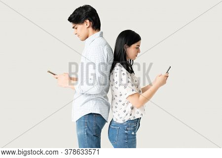 Angry Boyfriend And Girlfriend Ignoring Each Other And Using Phone After Argument