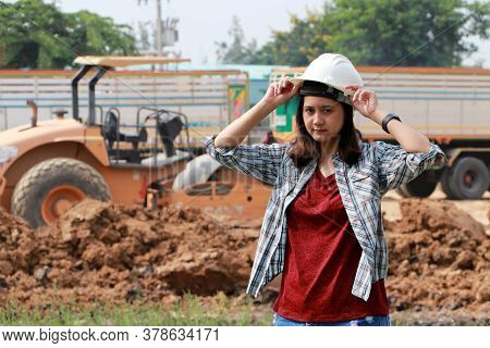 Female Civil Engineer Standing And Catch The White Helmet On Loader Pedal Car And Pile Of Soil Backg