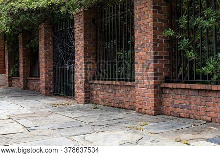 Tall Brick And Wrought Iron Wall Beside A Slate Stone Walkway, Old Architectural Details, Copy Space