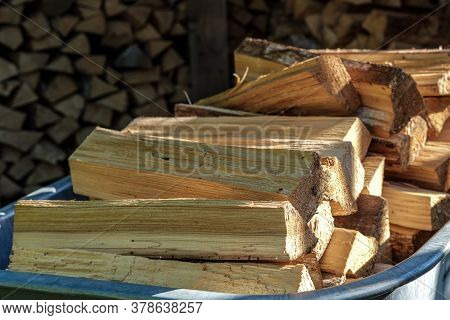 Birch Firewood Chopped Into Small Pieces For The Fireplace Insert, Lie In A Pile In A Metal Wheelbar