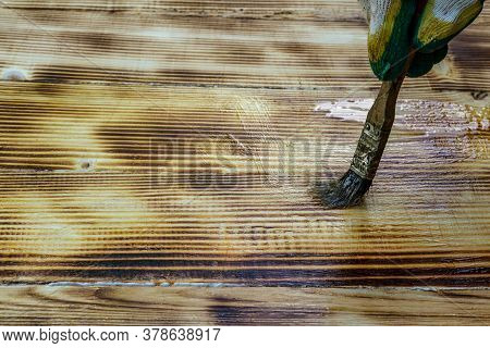 A Man (painter) Paints The Surface Of The Wooden Countertop With Varnish, Traces Of Throwing (burnin