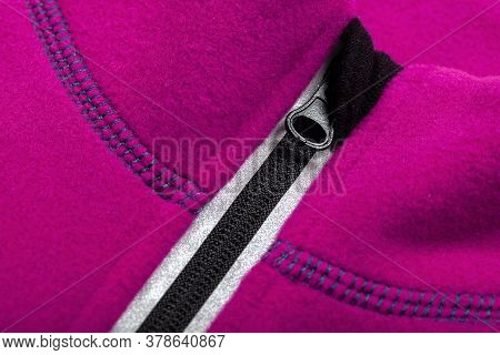 Zipper With Reflector Of A Pink Fleece Jacket, Close-up Photo