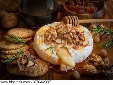 Cheese Board Served For An Appetizer: Baked Brie,crackers,jam And Nuts.