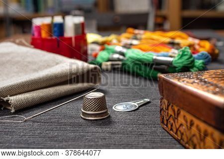 In The Foreground A Needle Lying On A Thimble. In The Background, Fabric And Multicolored Mouline Th