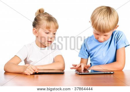 Elementary Boy And Girl Sitting At Table Using Digital Pads