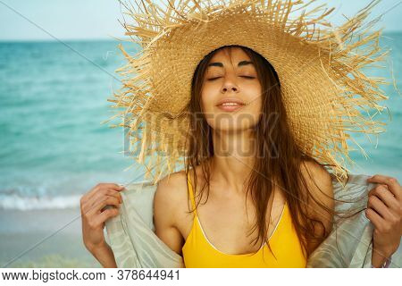 Close-up Outdoors Fashion Portrait Young Woman Wearing Big Straw Hat By Sea On Tropical Beach