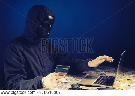 Anonymous Hacker In Mask Programmer Uses A Laptop To Hack The System In The Dark. The Concept Of Cyb