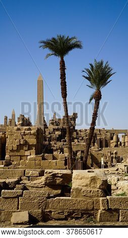 Karnak Temple Egypt Luxor  Landscape Obelisk Colum With Palm Trees Foreground And Architecture Ruins