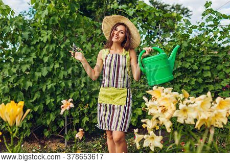 Woman Watering Flowers With Watering Can And Cutting With Pruner In Garden. Gardener Taking Care Of