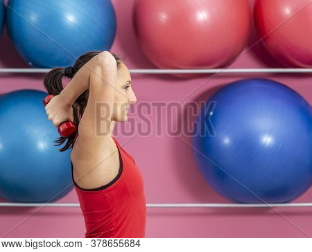 Young Woman Doing Exercises With Dumbbells In A Gym