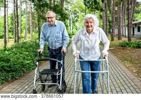Elderly Couple In The Park Strolling With Walkers