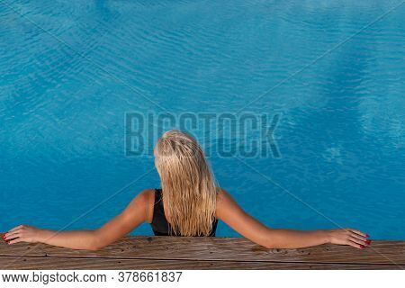 Sexy Woman In Bikini Relaxing In The Pool. Top View Of Lady In Swimsuit In Resort Poolside Of Luxury