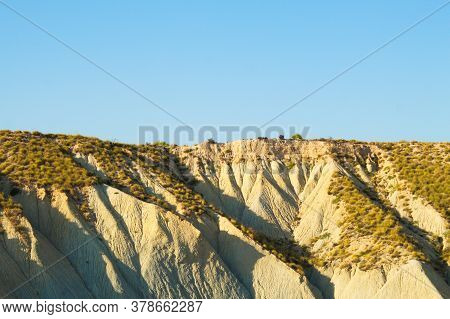 Desert Landscape Due To Climate Change With Arid Valleys And Dry Vegetation