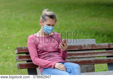 Woman With A Medical Mask On Her Face Sits On A Park Bench And Looks At The Phone, Quarantine, Covid