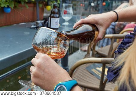 ROTTERDAM, THE NETHERLANDS - SEPTEMBER 22, 2019: La Trappe Dutch Trappist abbey beer poured into a glass on an outdoor terrace