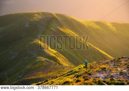 Beautiful Mountains In Fog And Standing Woman With Backpack On The Mountain Peak At Sunset In Summer