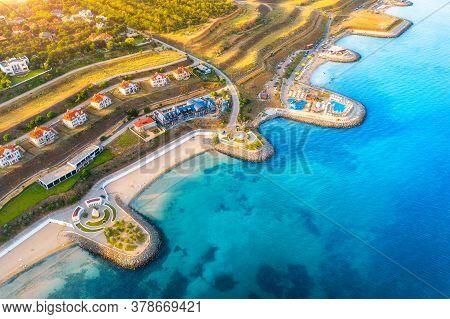 Aerial View Of Beautiful Sandy Beach, Blue Sea, Promenade, Houses, Pool, Umbrellas, Water, Green Tre