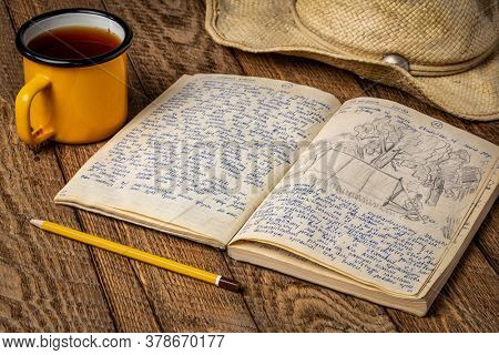 Vintage expedition journal on a rustic picnic table with a cup of tea and straw hat - handwriting and drawing in travel log from 1974 paddling trip in Poland (property realease attached).