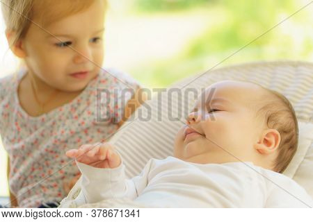 Cute Little Girl Kissing His Newborn Sister. Toddler Kid Meeting New Born Sibling. Infant Sleeping I