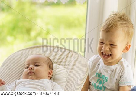 Cute Little Baby Boy With Newborn Sister. Toddler Kid Meeting New Born Sibling. Infant Sleeping In W