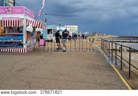 Hunstanton, Norfolk, England, Uk - July 25, 2020: People Walking On The Beach On A Cloudy Summer Day