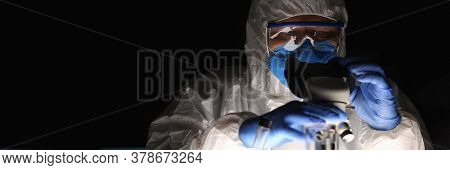 Man In Protective Suit Conducts An Experiment. Manufacture Drugs Assessment Their Originality And Qu