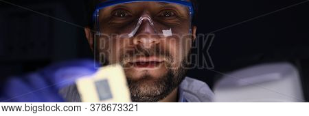 Portrait Of Concentrated Professional Technician In Uniform At Work. Man In Eye-glasses Looking Atte