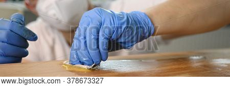 Male Carpenter Rubs Mixture On Wooden Surface. Man Performs Variety Operations With Timber. Producti