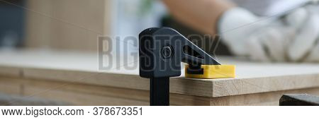 Close-up Of Building Vise With Wooden Plank. Woodworker In Protective Gloves Grinding Wood Surface.