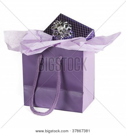Present wrapped in purple & silver paper in purple gift bag