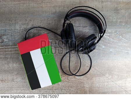Headphones And Book. The Book Has A Cover In The Form Of Arab Emirates Flag. Concept Audiobooks. Lea